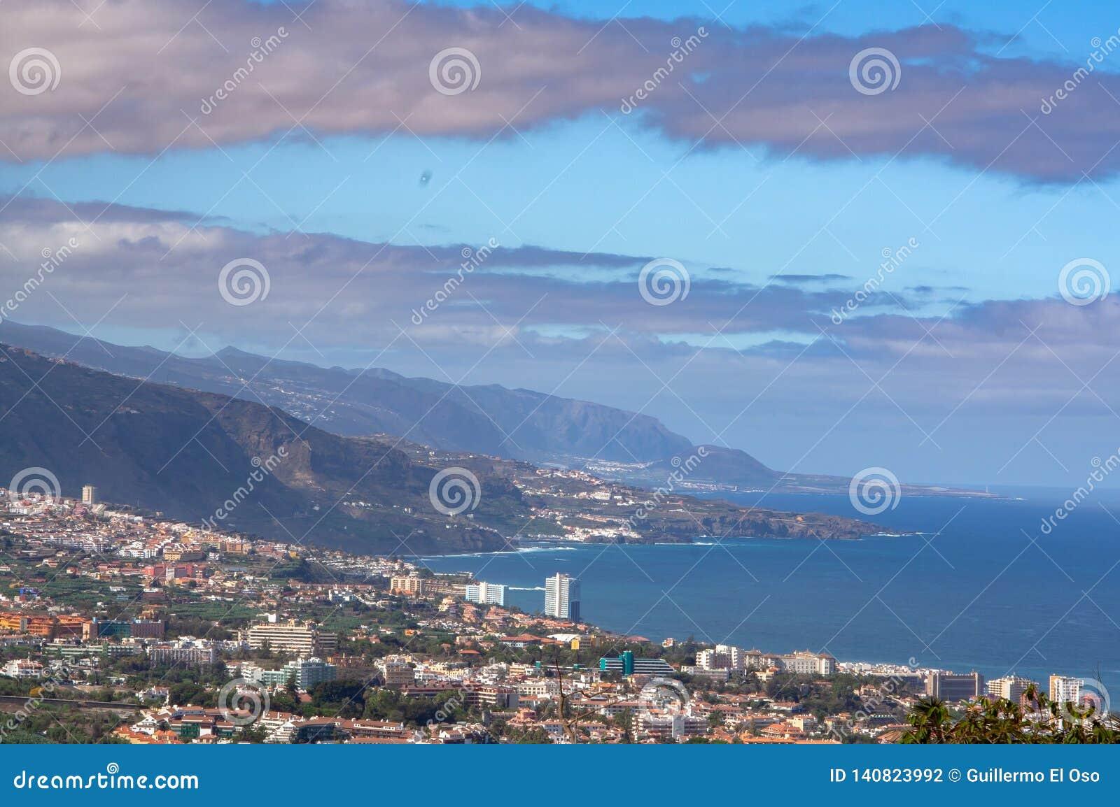 Avlägsen sikt från ett berg på lös kust med staden