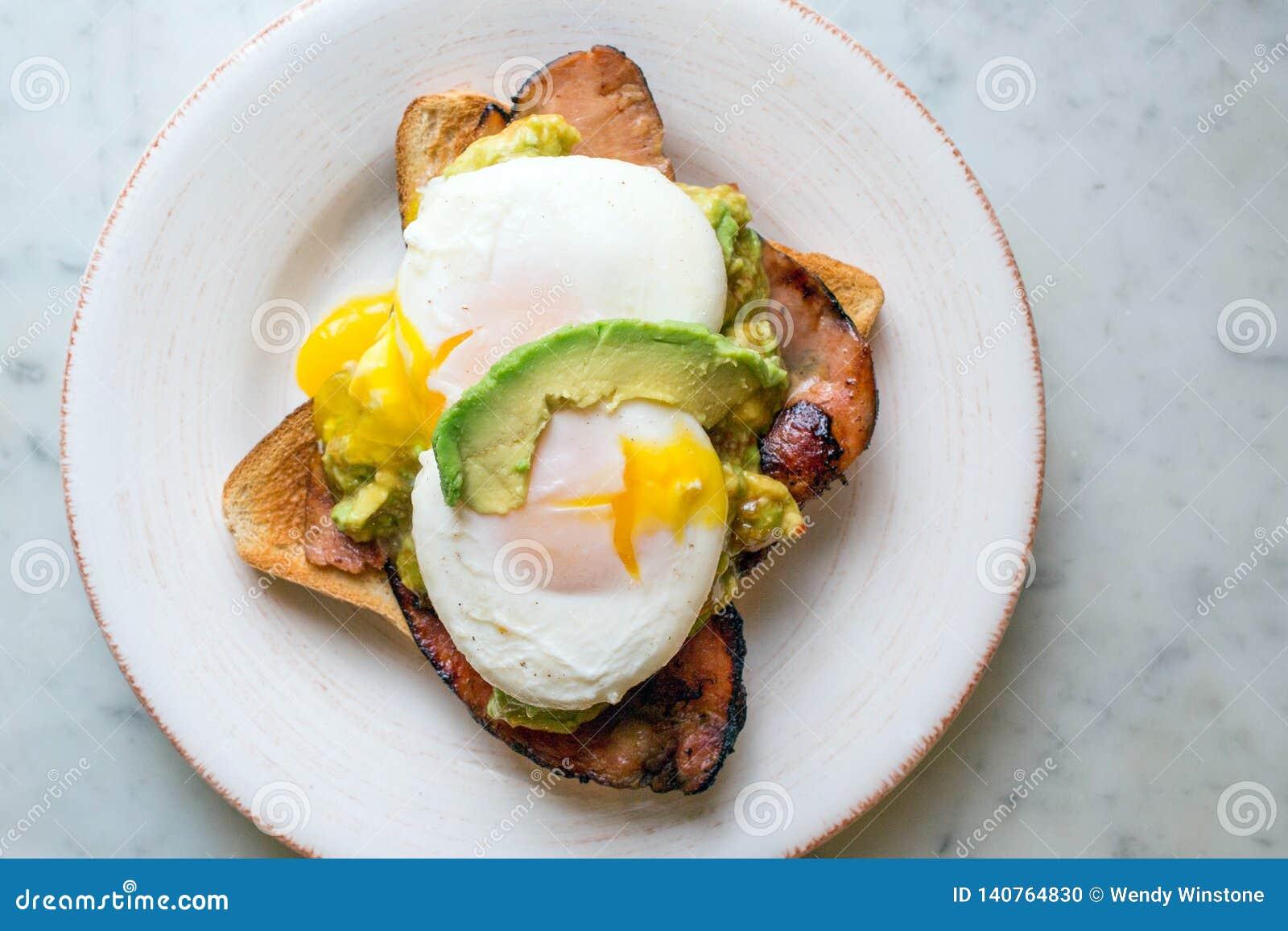 Avocado con le uova ed il bacon pouched su pane tostato