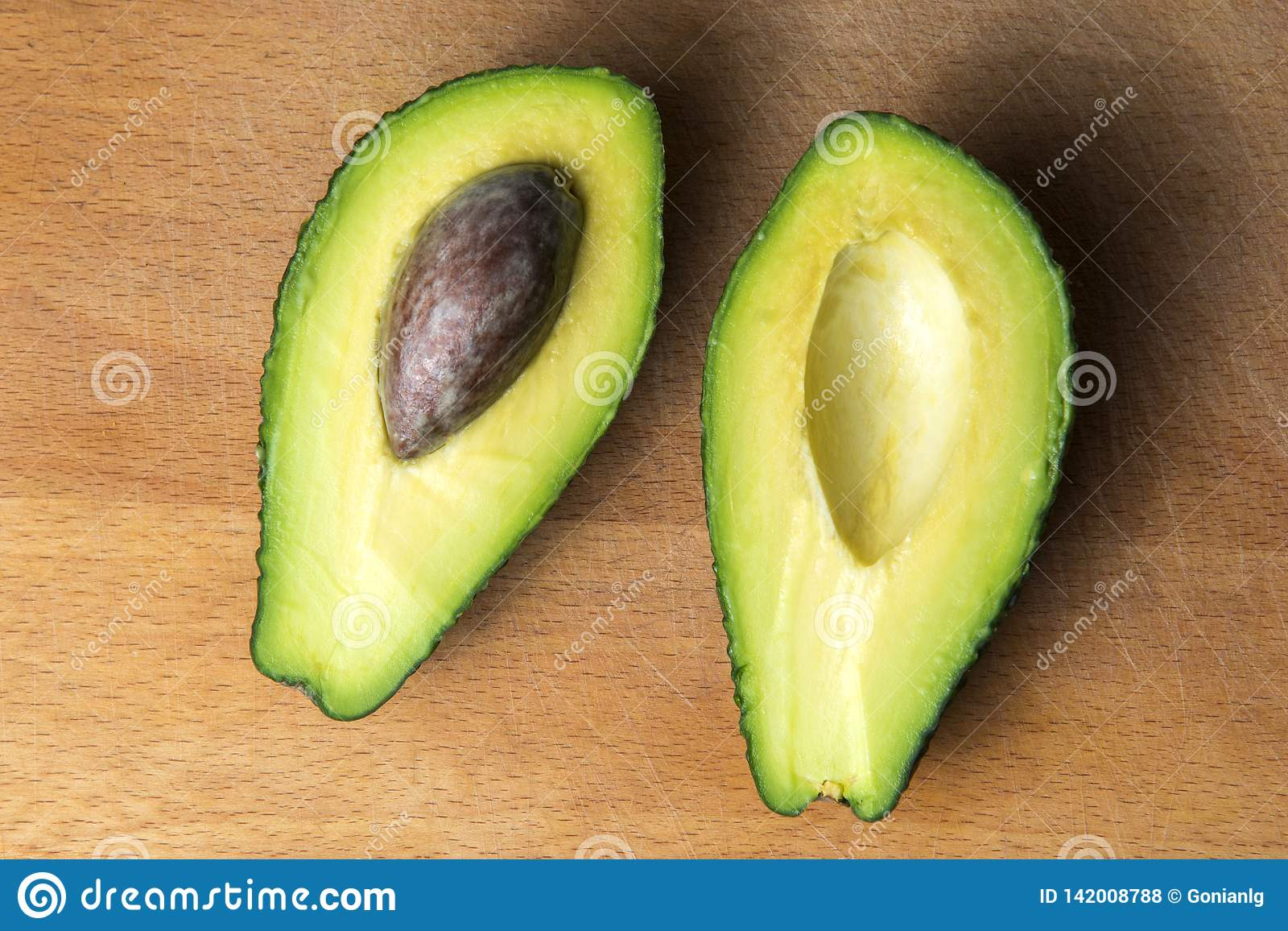 Avocado cut into 2 pieces on the kitchen board