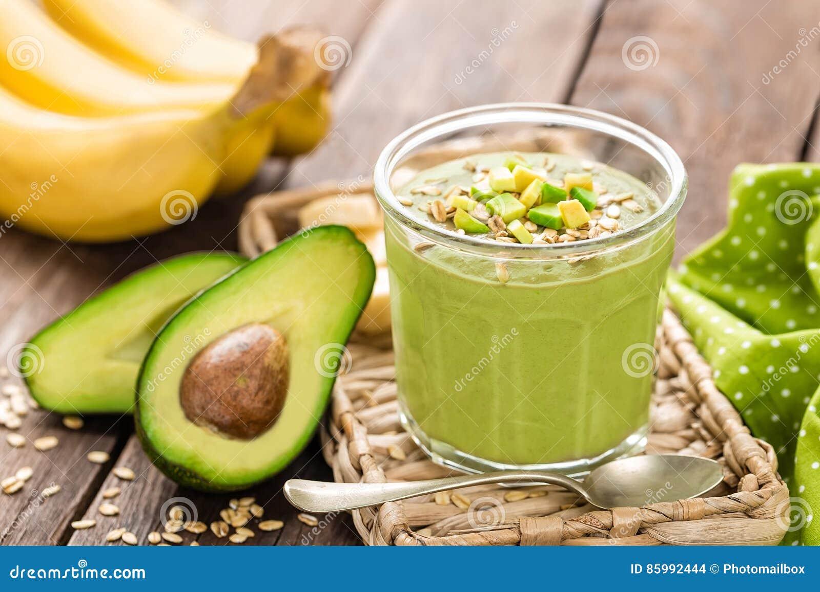 Avocado en banaan smoothie met haver met ingrediënten in glaskruik op houten achtergrond