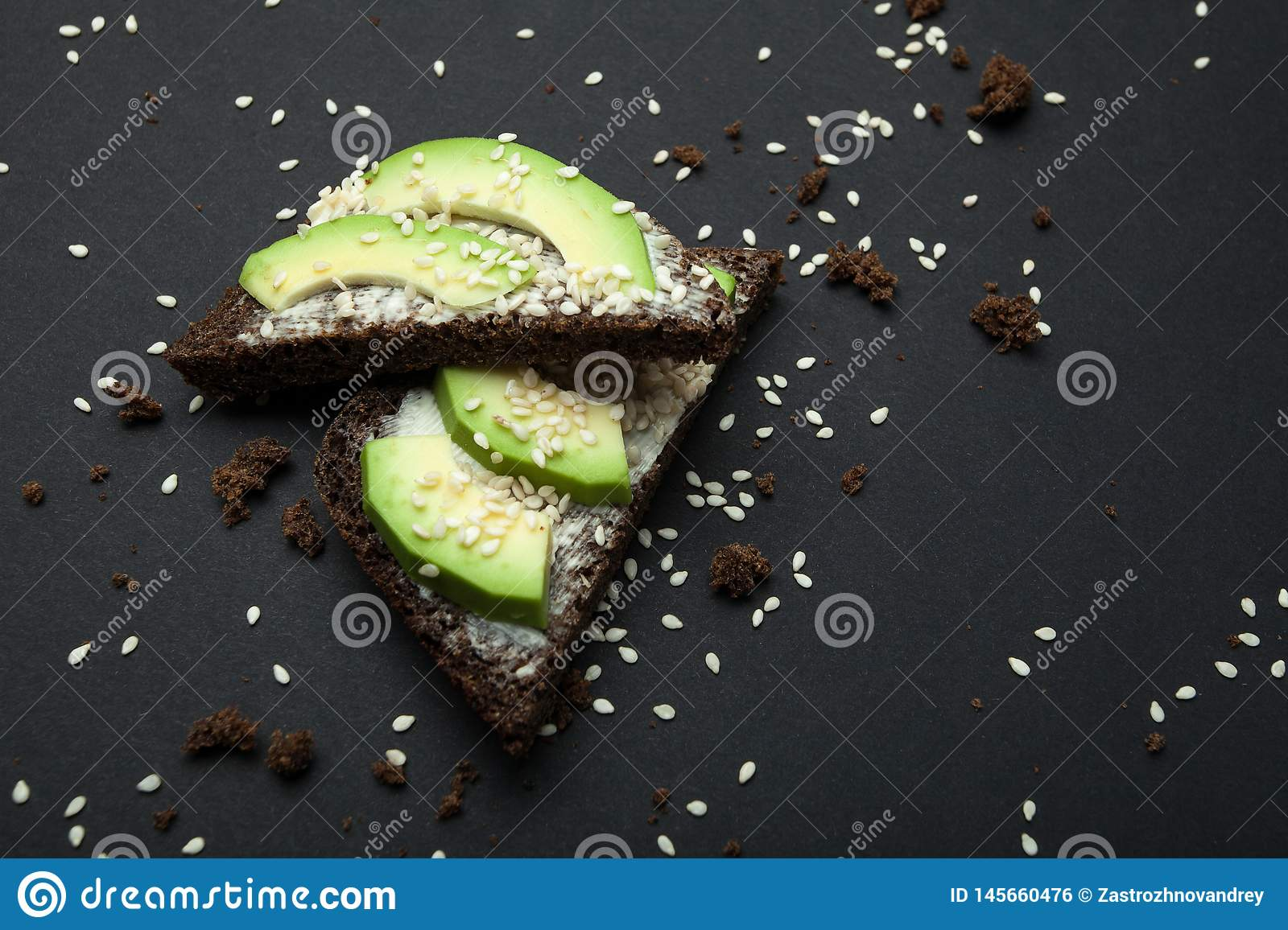 Avocado sandwich with sesame seeds and black bread isolated on a black background