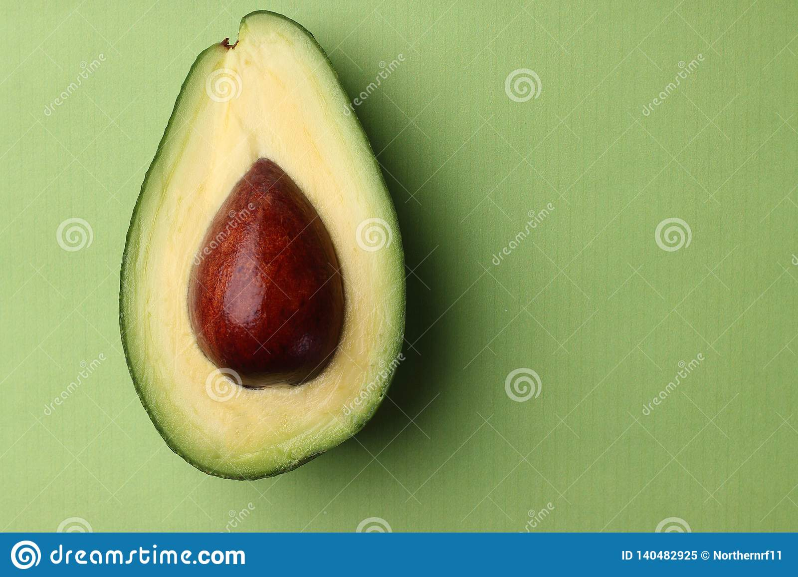 Avocado with seed on green. half avocado on green background