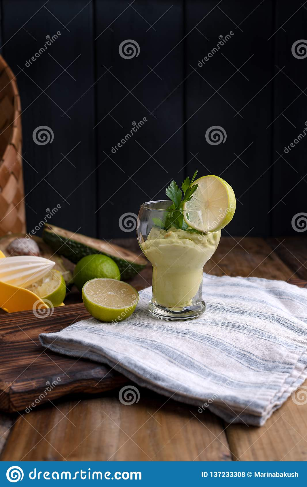 Avocado smoothie and lime in a glass. Food for health and beauty. Super food from vegetables and fruits. Wooden background, free