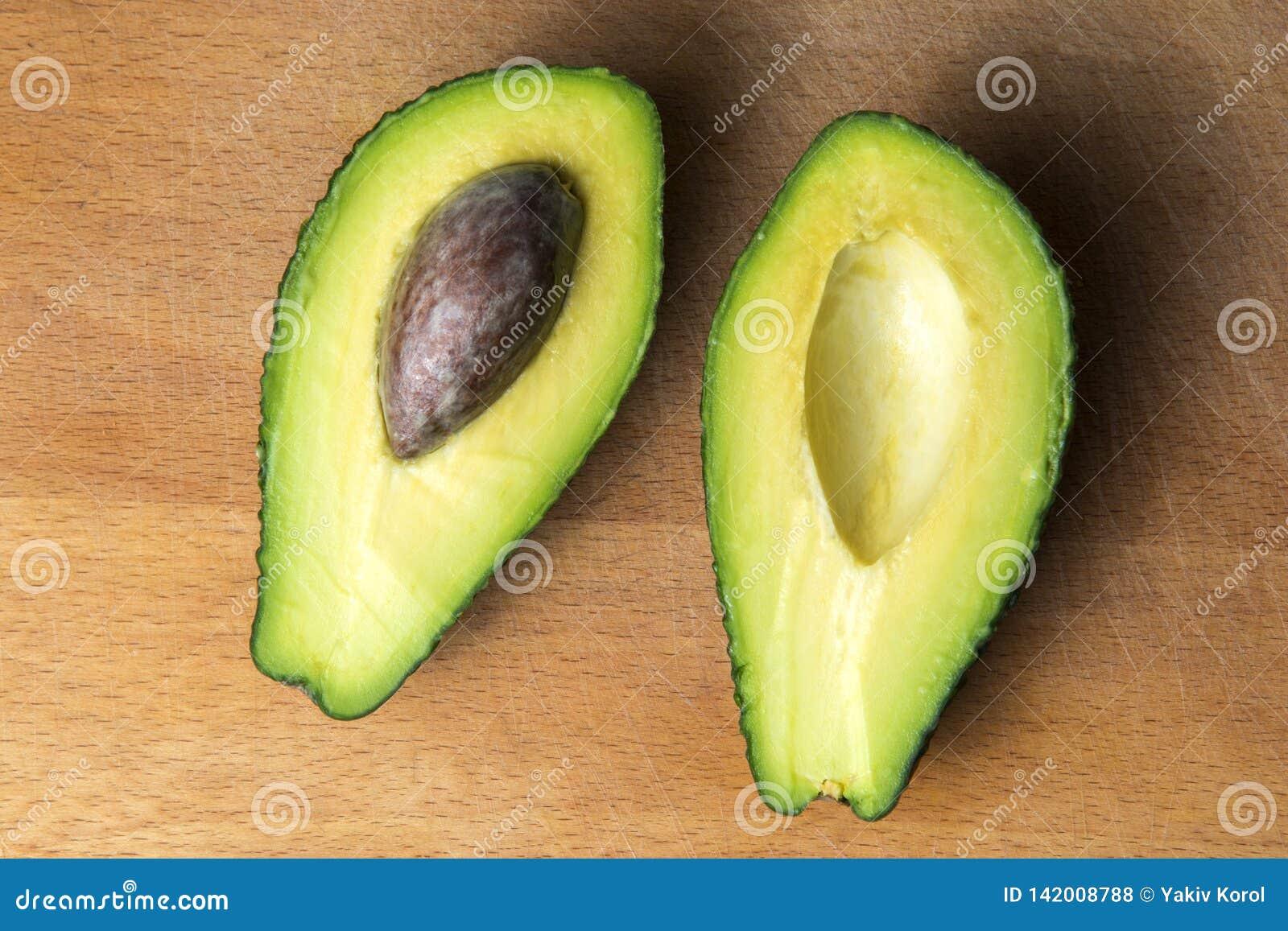Avocado in 2 stukken op de keukenraad die wordt gesneden