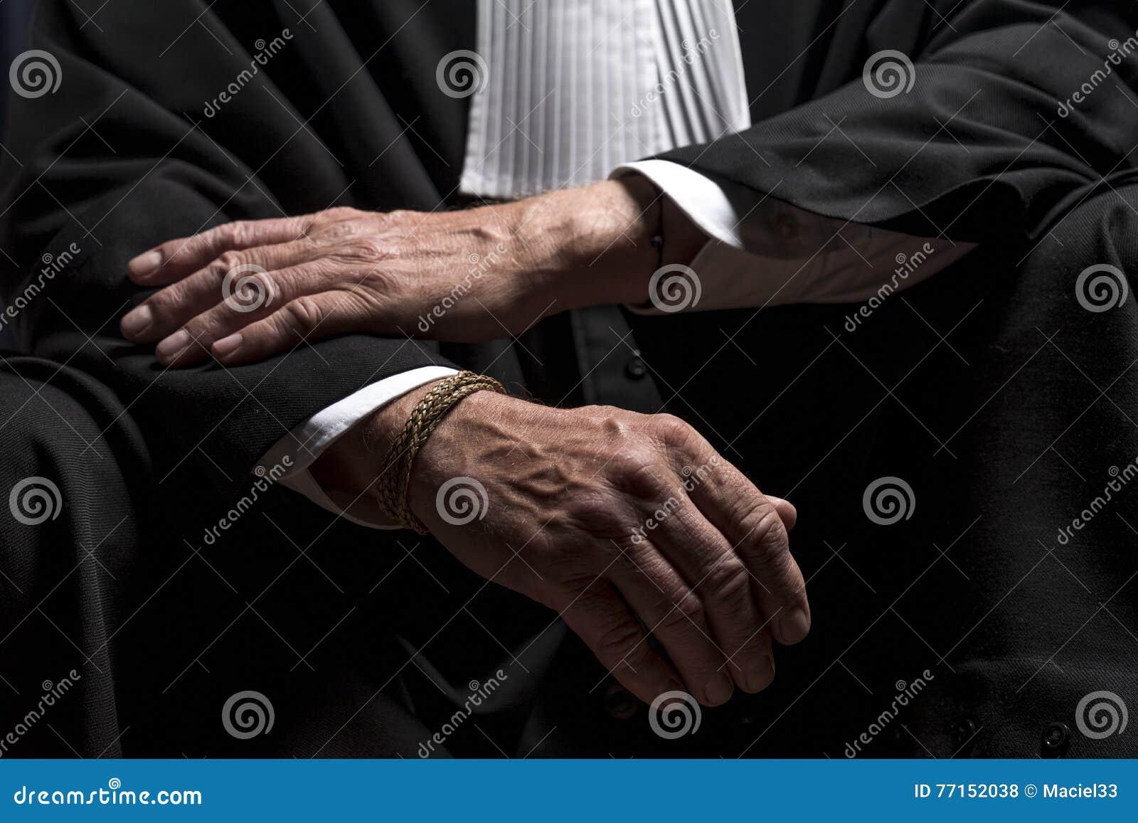 Avocat dans la robe avec le juge haut étroit de mains de jabot