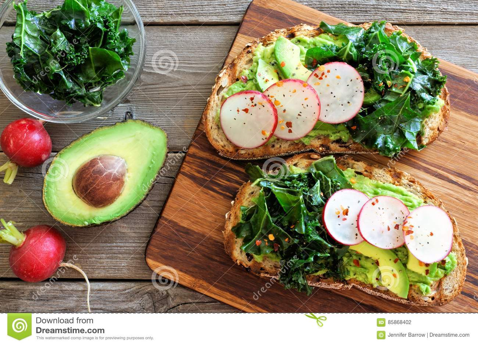 Avokadorostat bröd med grönkål och rädisan över lantligt trä