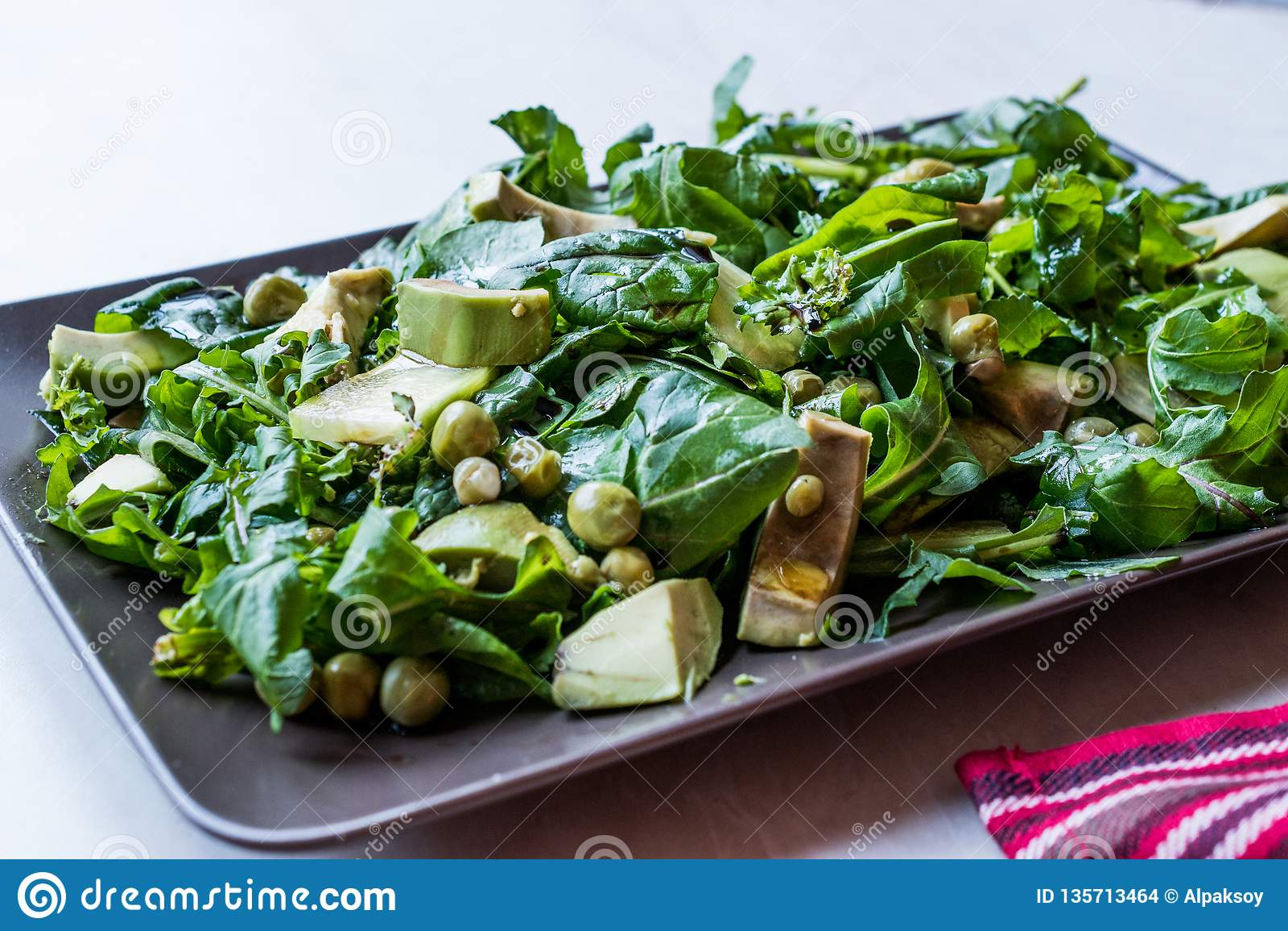 Avokadosallad med gröna ärtor och Rocket Leaves i rektangulära platta/Arugula eller Rucola sidor