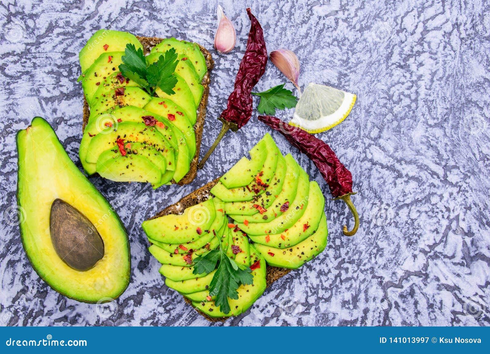 Avokadosmörgåsar på en grå bakgrund, kryddor, citron Top beskådar