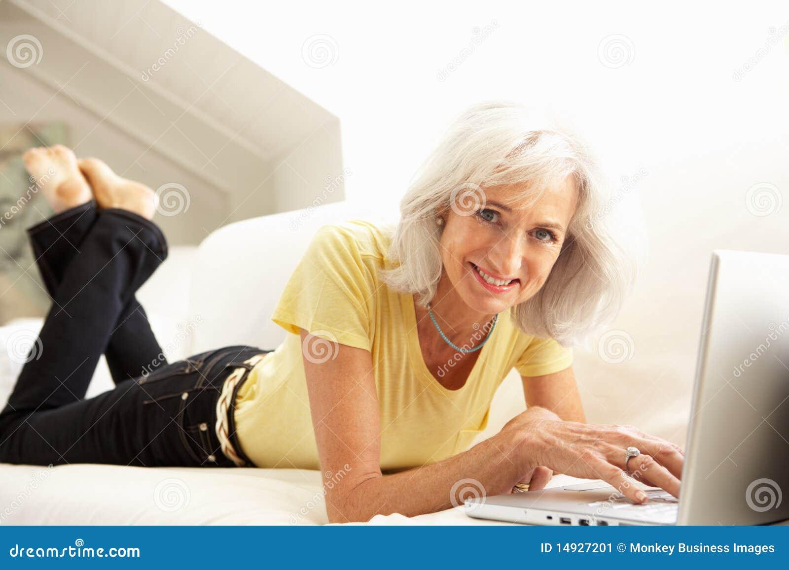 Avslappnande hög sittande sofa för bärbar dator genom att använda kvinnan