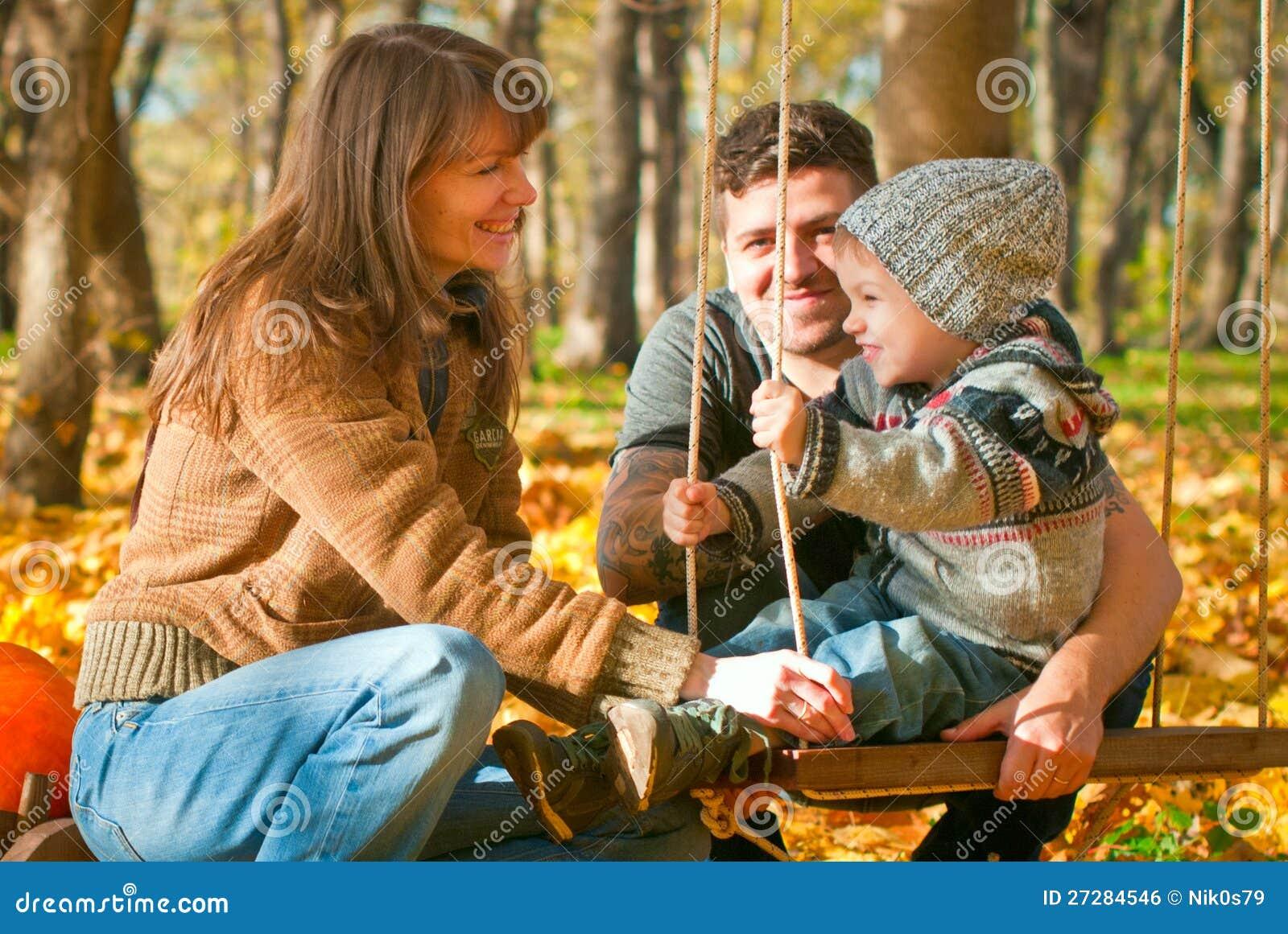 Avslappnande lycklig familj utomhus