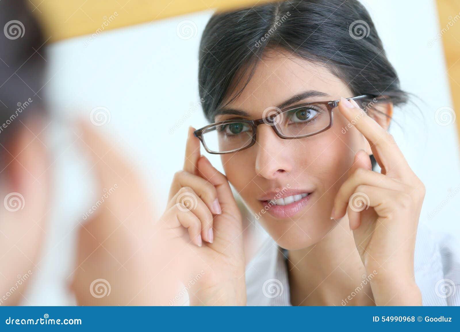 Avspegla ståenden av den unga kvinnan som försöker på glasögon