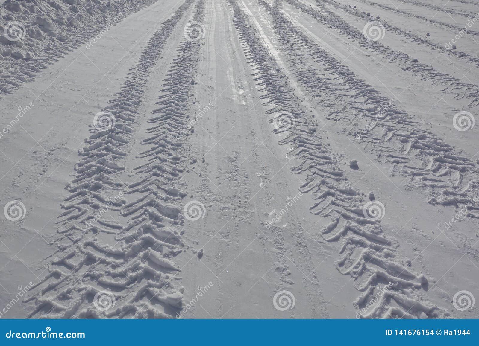 Avtryck av ett lastbilgummihjul på den snöig vägen i vinter