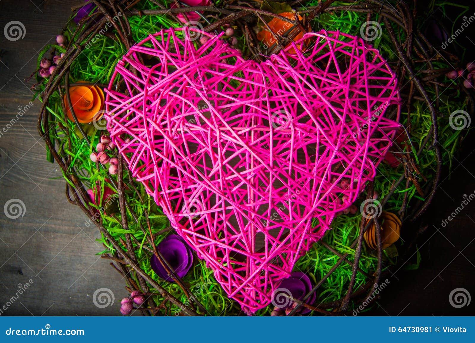 Avvolga in una forma di cuore fatta da erba