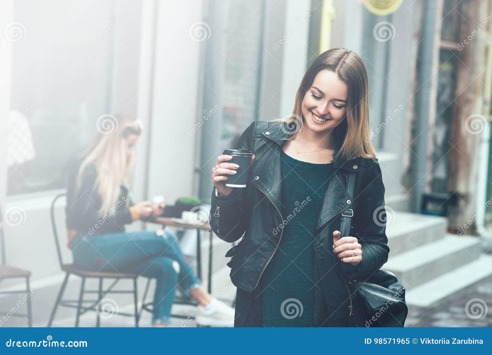 Away kaffetake Härlig ung stads- kvinna som bär i svart stilfull kläder som rymmer kaffekoppen och ler, medan promenera