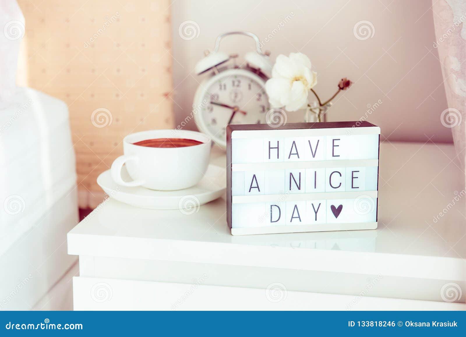 Ayez un message de beau jour sur la boîte allumée, le réveil, la tasse de café et la fleur sur la table de chevet dans la lumière