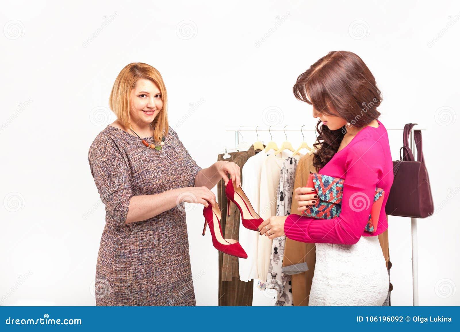 Ayuda que hace compras Estilista hermoso cerca del estante con las suspensiones