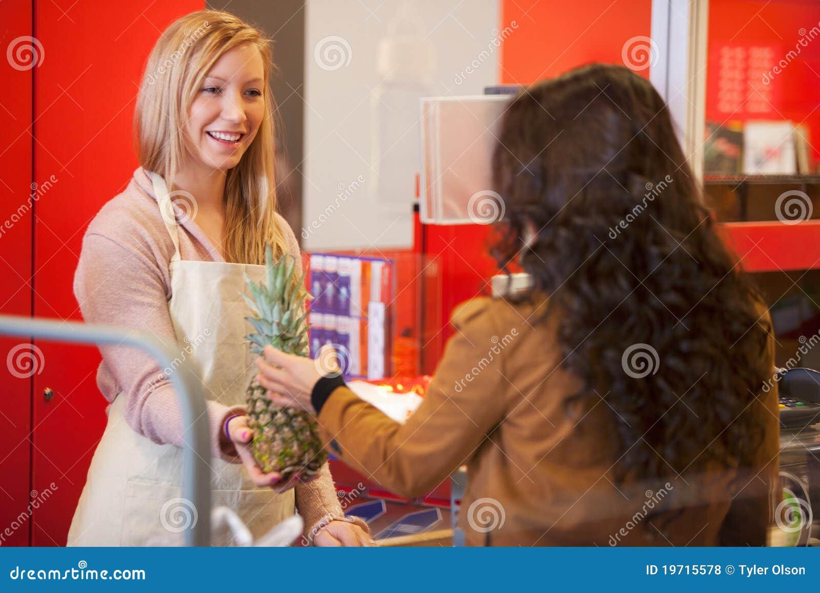 Ayudante de departamento feliz con el cliente en supermercado