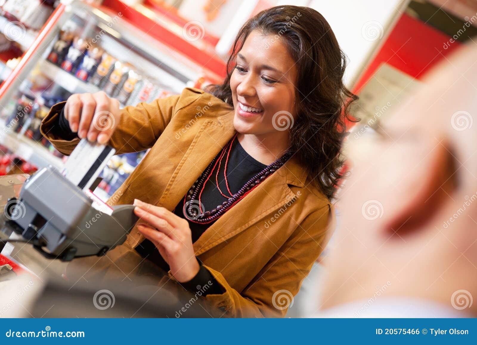 Ayudante de departamento que sonríe mientras que birla de la tarjeta de crédito