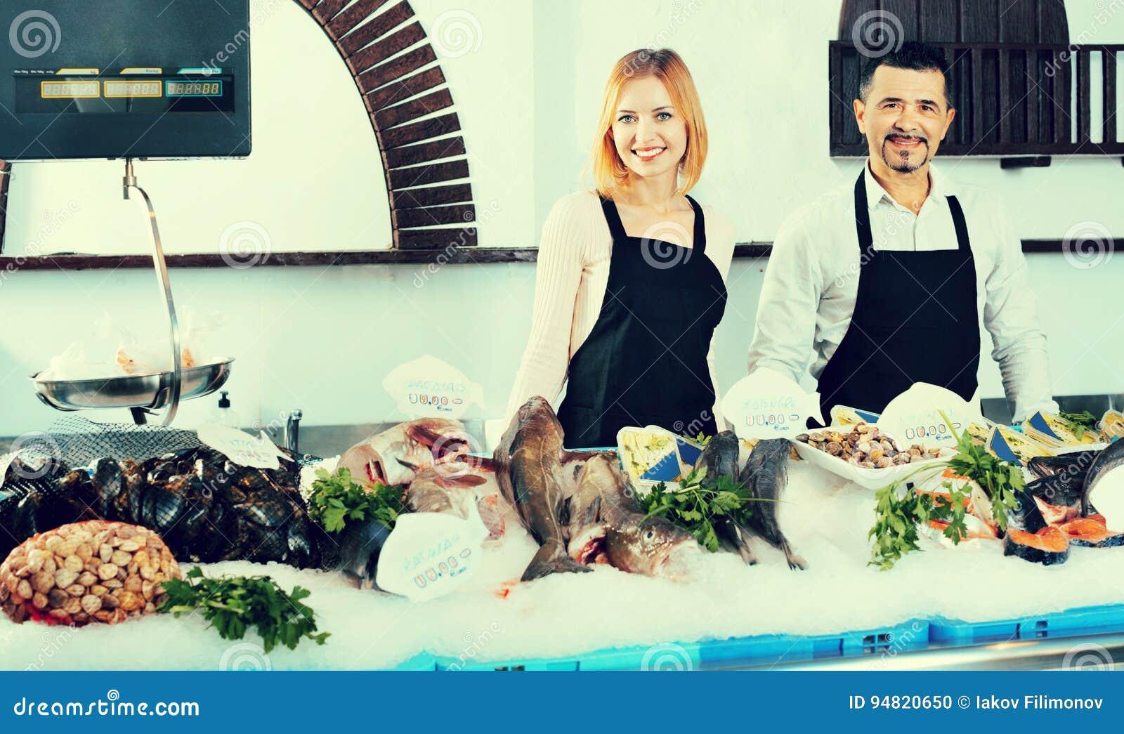 Ayudantes de tienda alegres sonrientes que venden pescados frescos