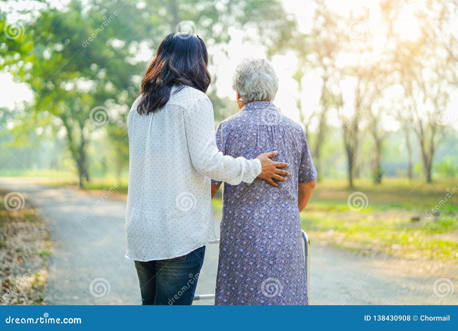 Ayude y cuide al caminante mayor o mayor asiático del uso de la mujer de la señora mayor con salud fuerte mientras que camina en