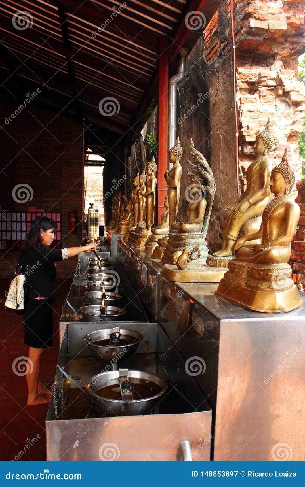 Ayutthaya, Tha?lande - 29 avril 2014 La femme dans le temple bouddhiste allume un allumeur en tant qu offre