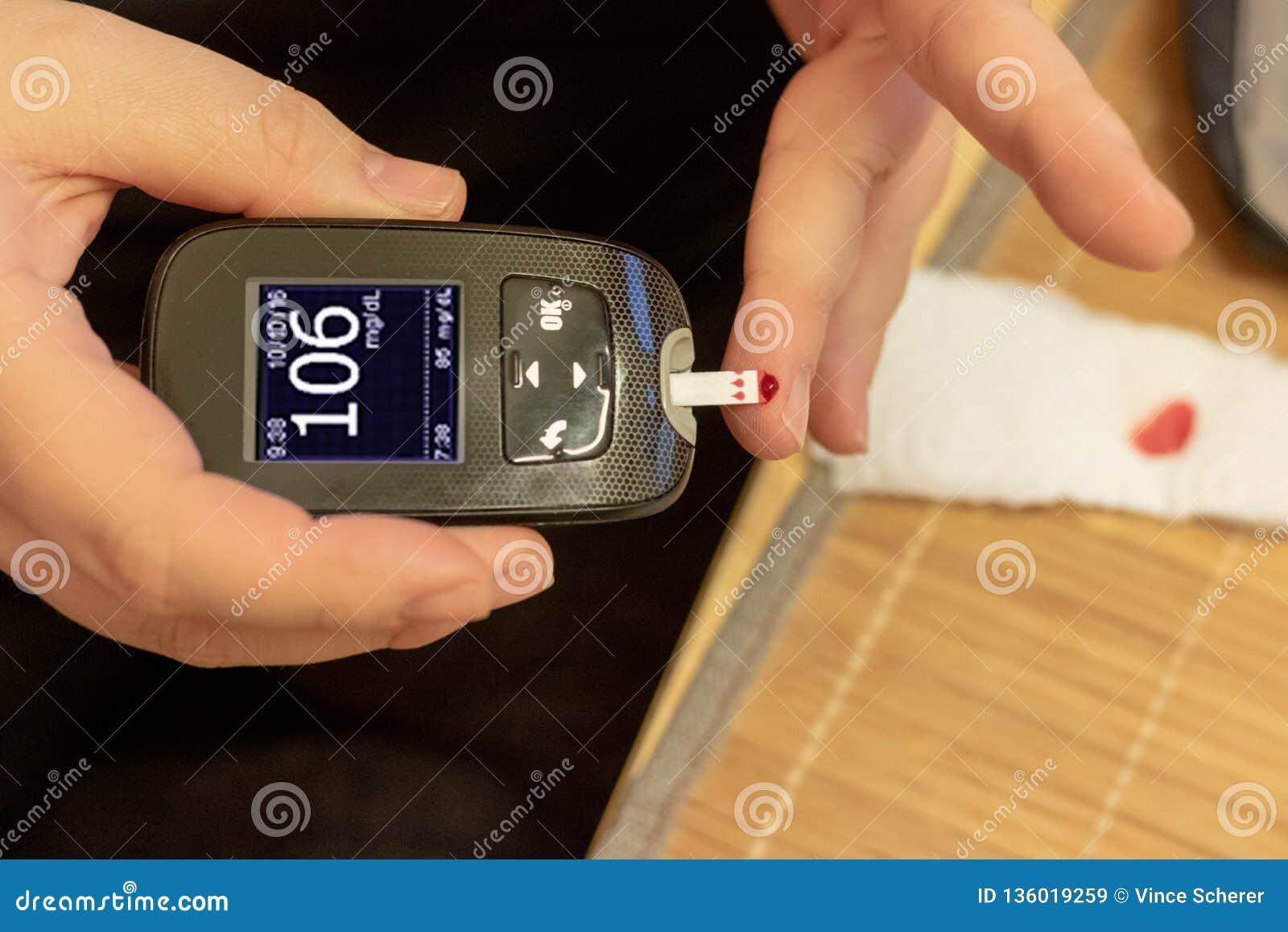 Azúcar de sangre de medición para las manos de la mujer de la diabetes
