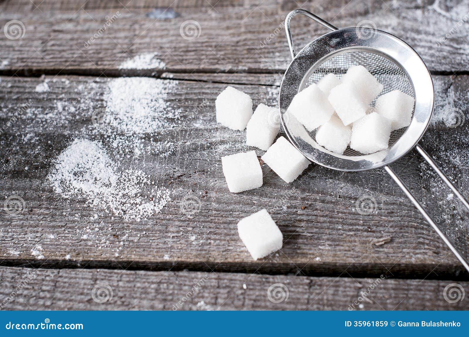 Azúcar de terrón en un tamiz s del metal en fondo de madera.