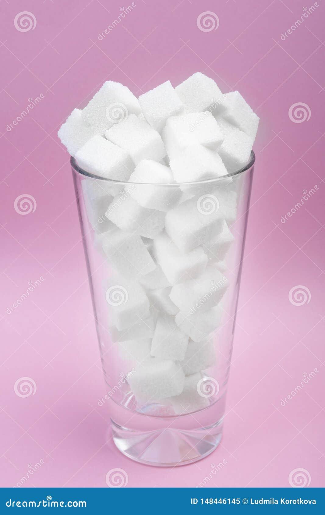 Azúcar en un vidrio de soda El consumo excesivo del azúcar lleva a la obesidad Consumici?n sana