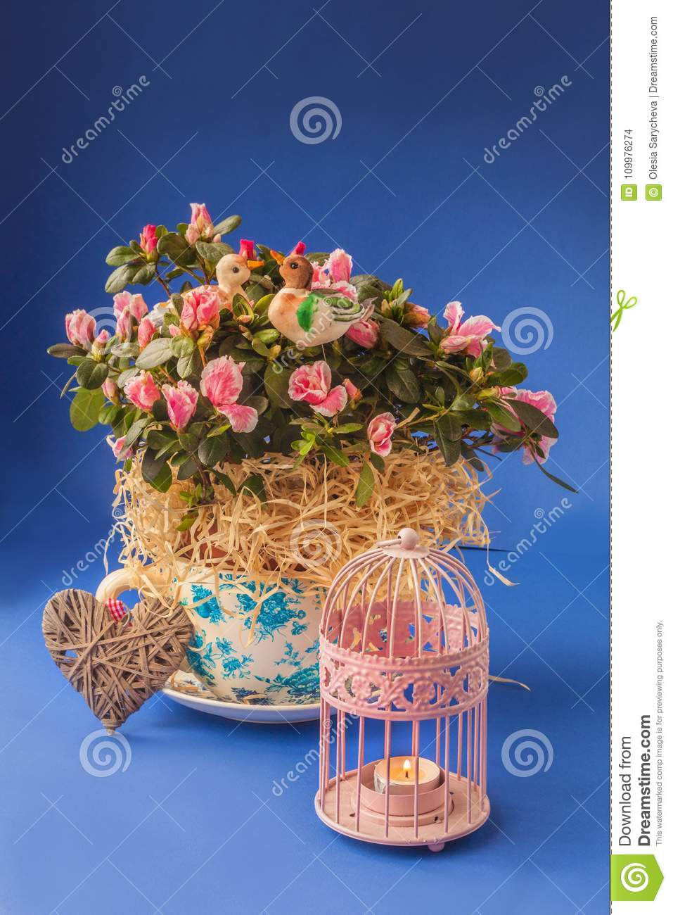 Azalea rhododendron in vintage pot and candlestick on a blue