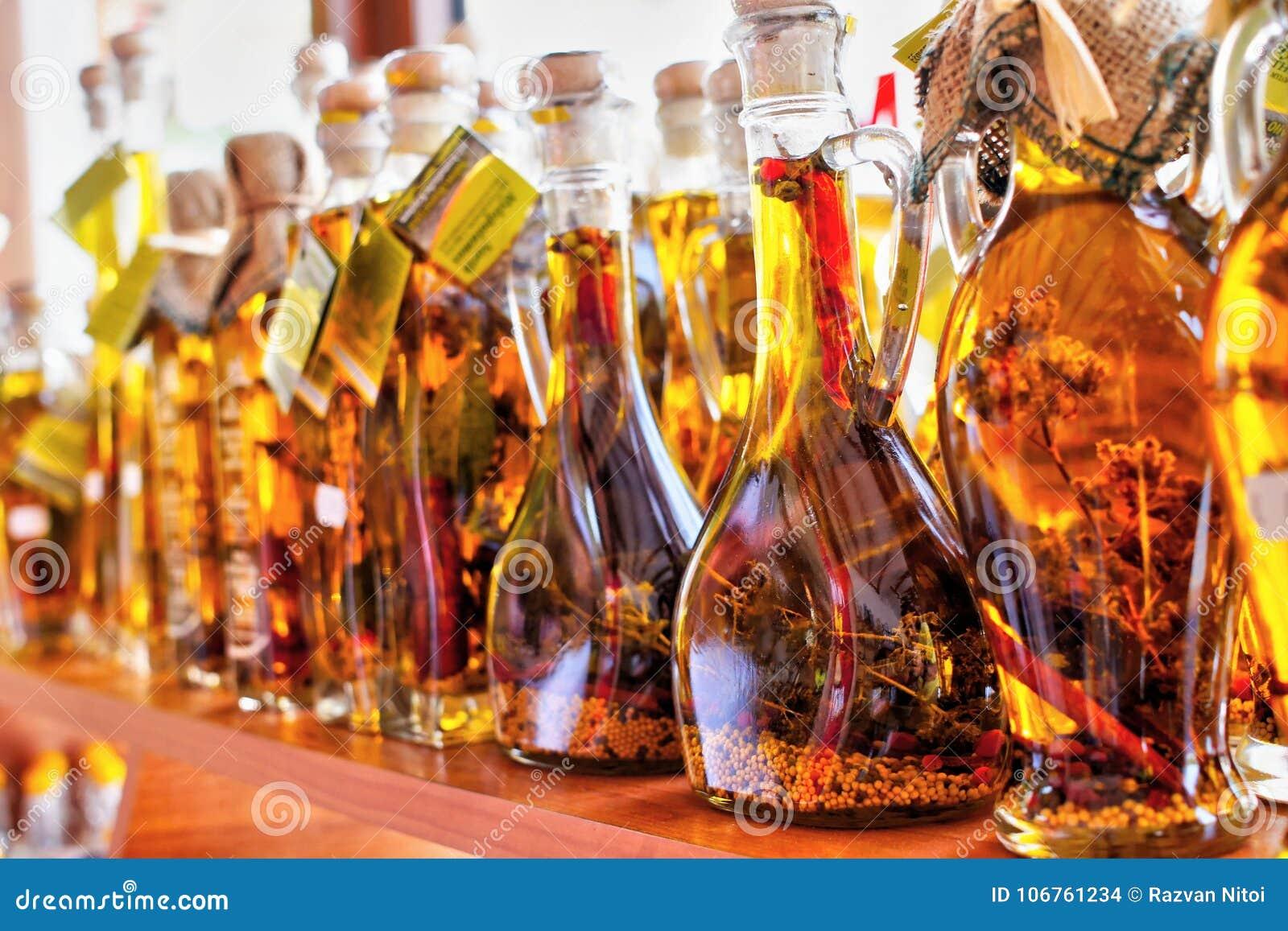 Azeite dourado com as especiarias em umas garrafas em Grécia