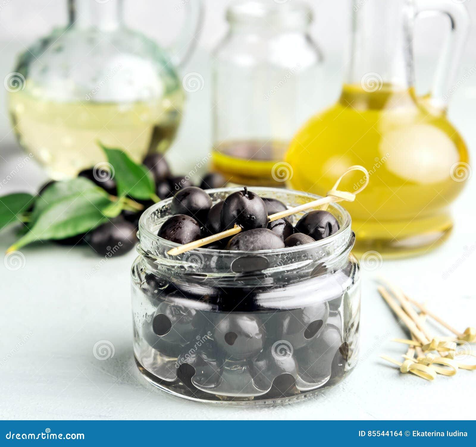 Azeite em umas garrafas com copyspace das azeitonas pretas e das folhas no fundo