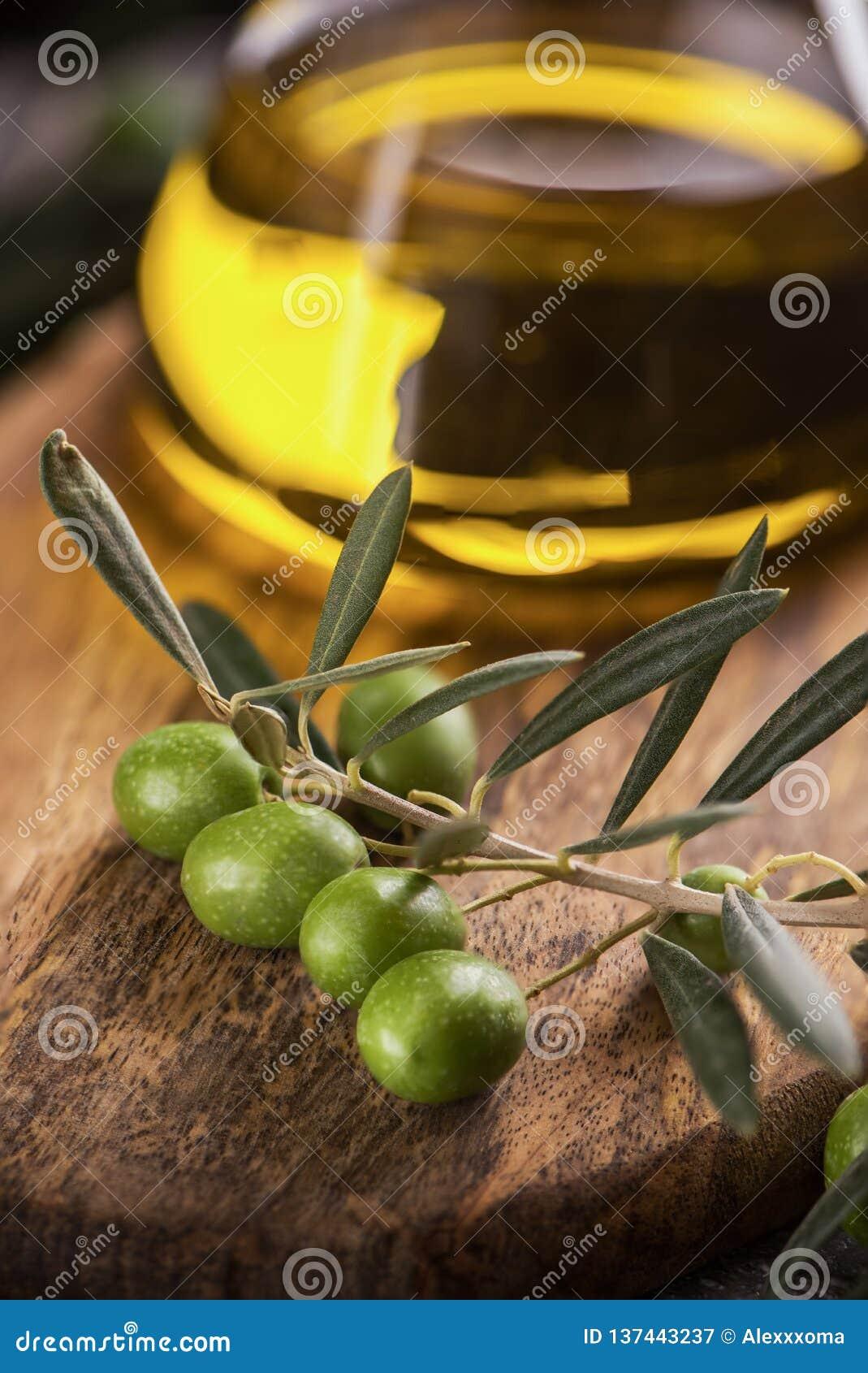 Azeite virgem extra na garrafa de vidro com ramo das azeitonas no fundo rústico