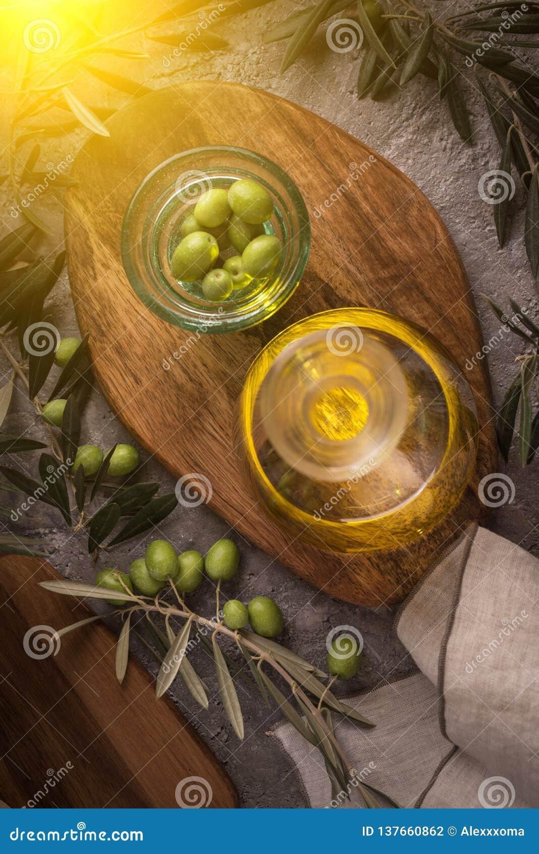 Azeite virgem extra na garrafa de vidro com ramo das azeitonas no fundo rústico baixa chave com brilho do sol do lado esquerdo