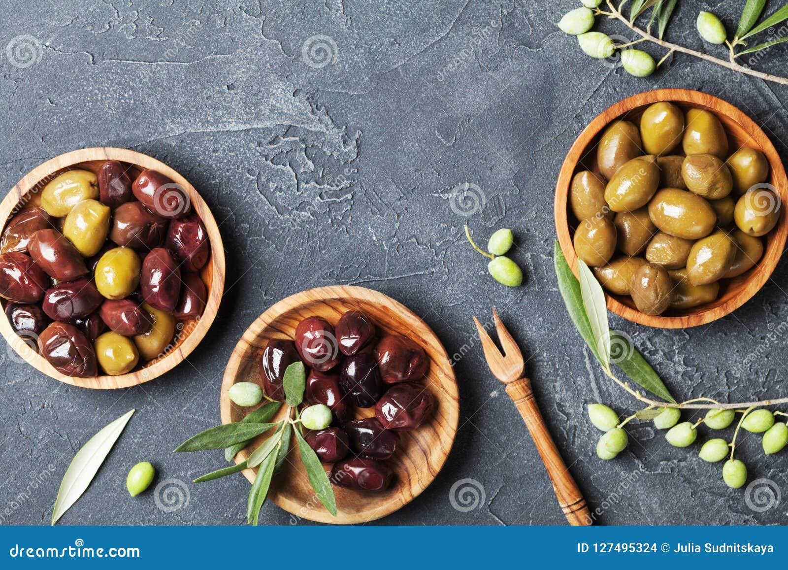 Azeitonas naturais em umas bacias com ramo de oliveira na opinião de tampo da mesa de pedra preta