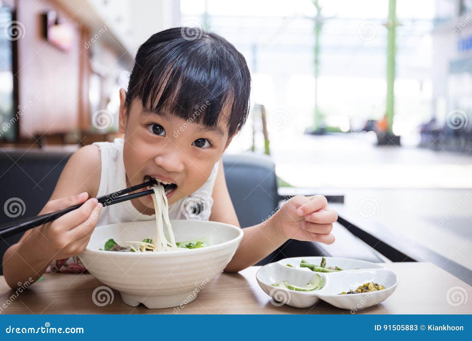 Aziaat weinig Chinees meisje die de soep van rundvleesnoedels eten
