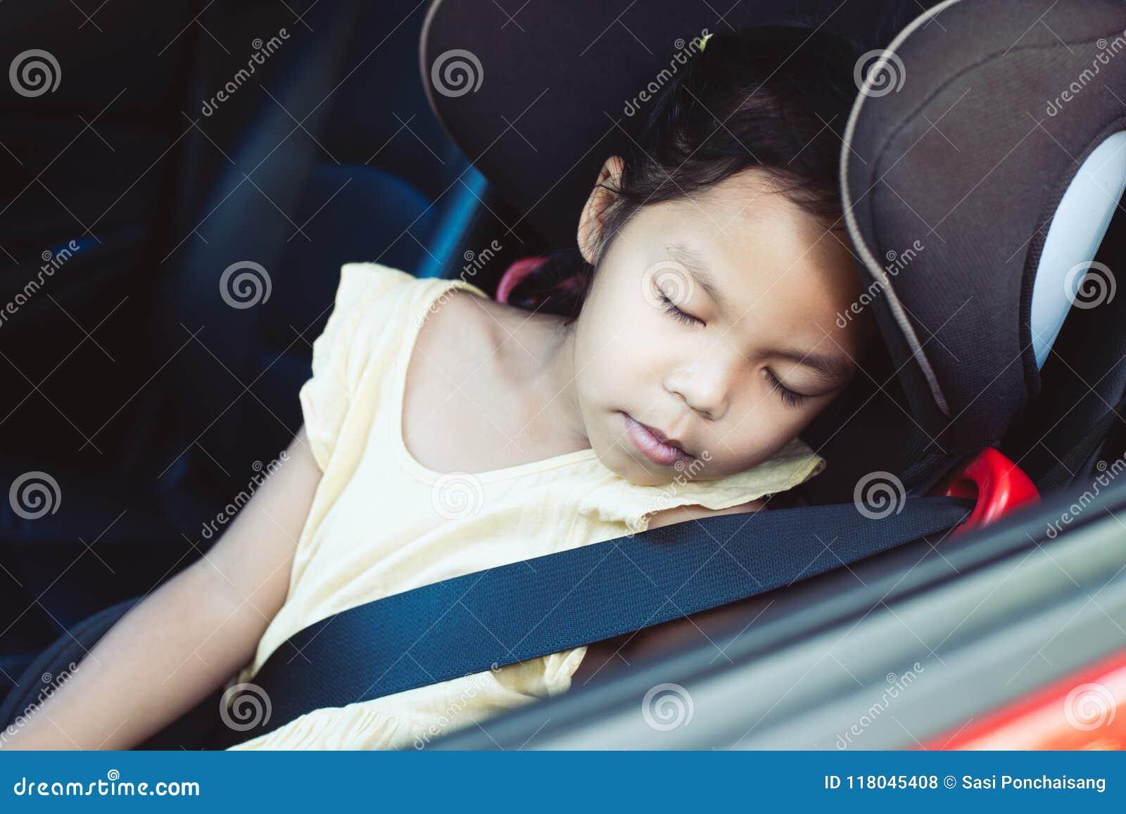 Aziaat weinig zitting van het kindmeisje in de autozetel en slaap