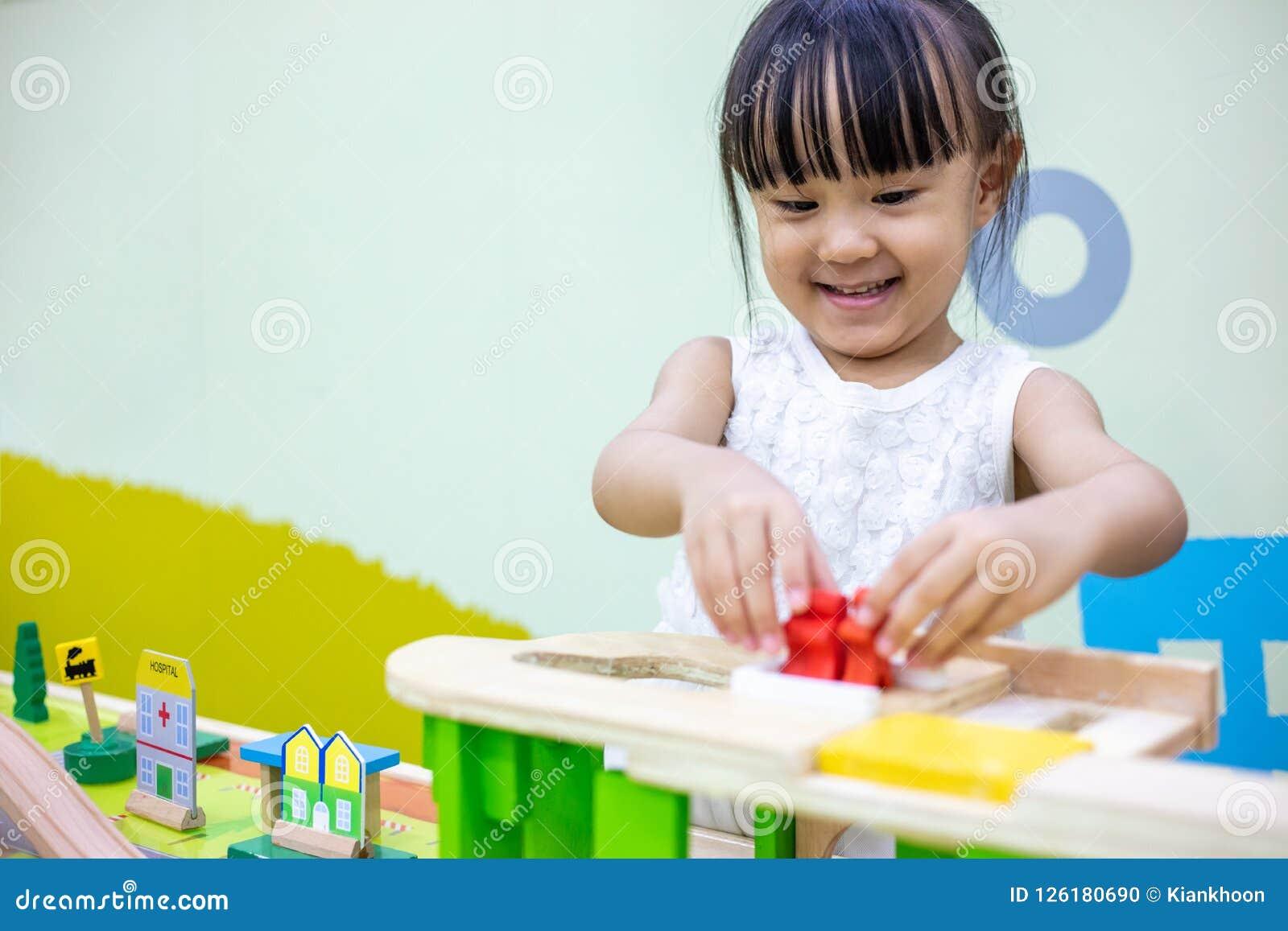 Aziatisch Chinees meisje die houten stuk speelgoed trein spelen