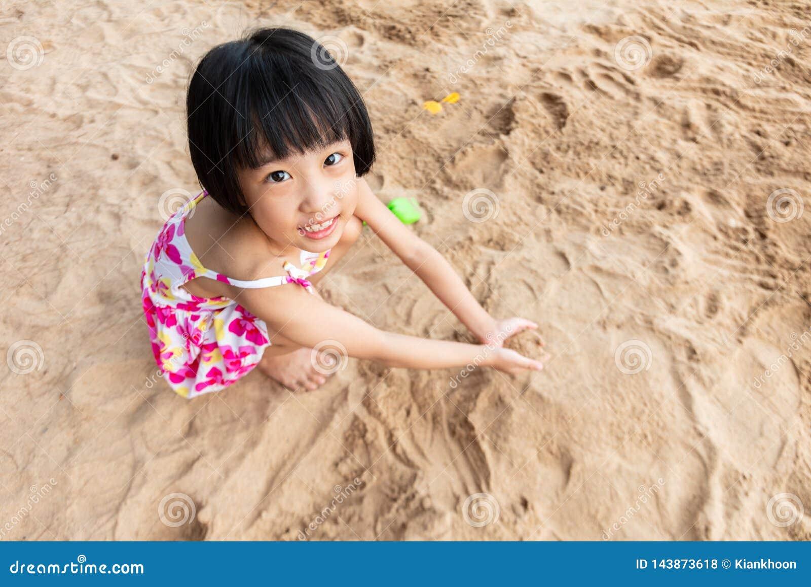 Aziatisch Chinees meisje het spelen zand bij strand