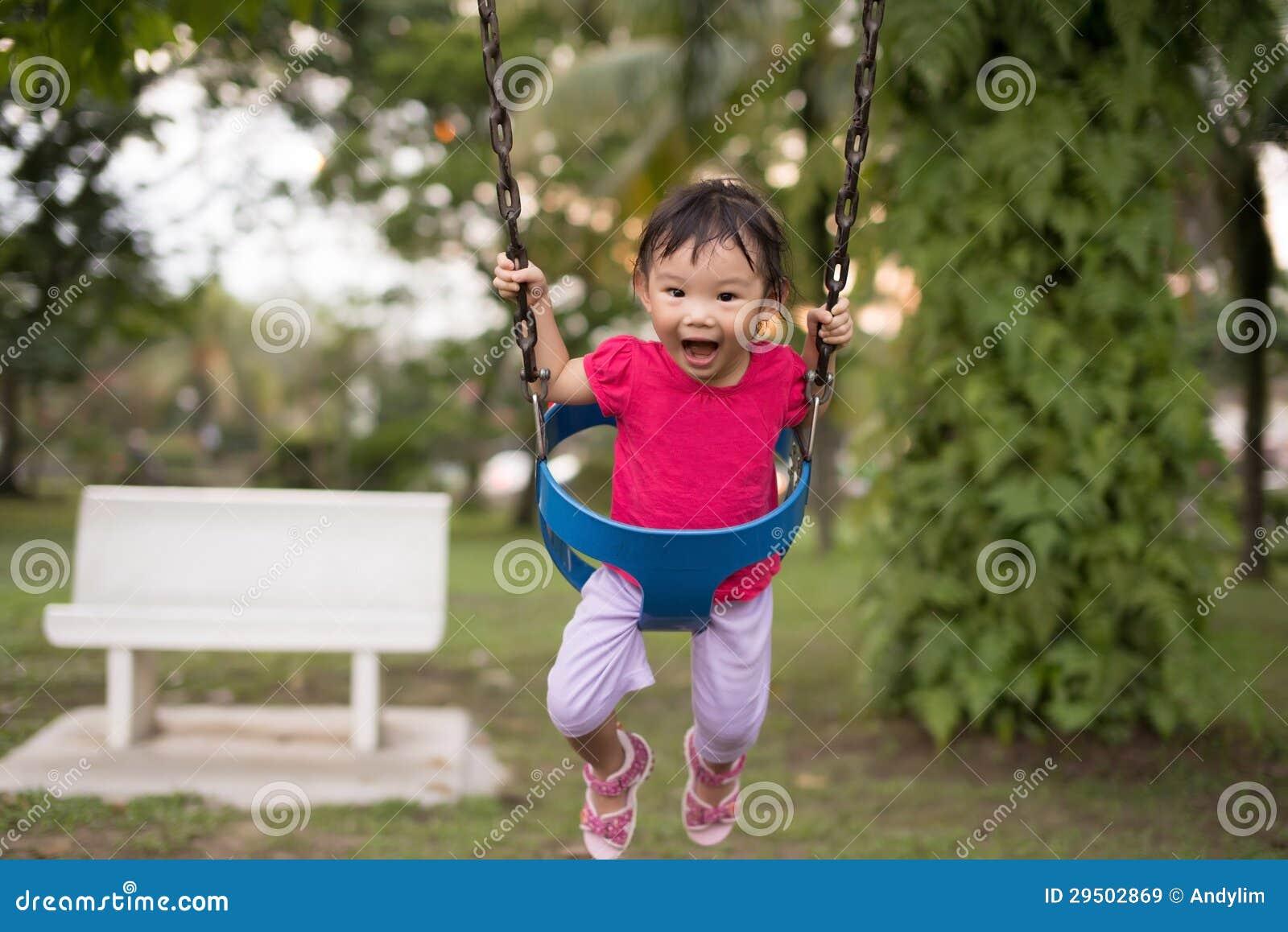Aziatisch Chinees oud meisje van twee jaar op een schommeling in de speelplaats