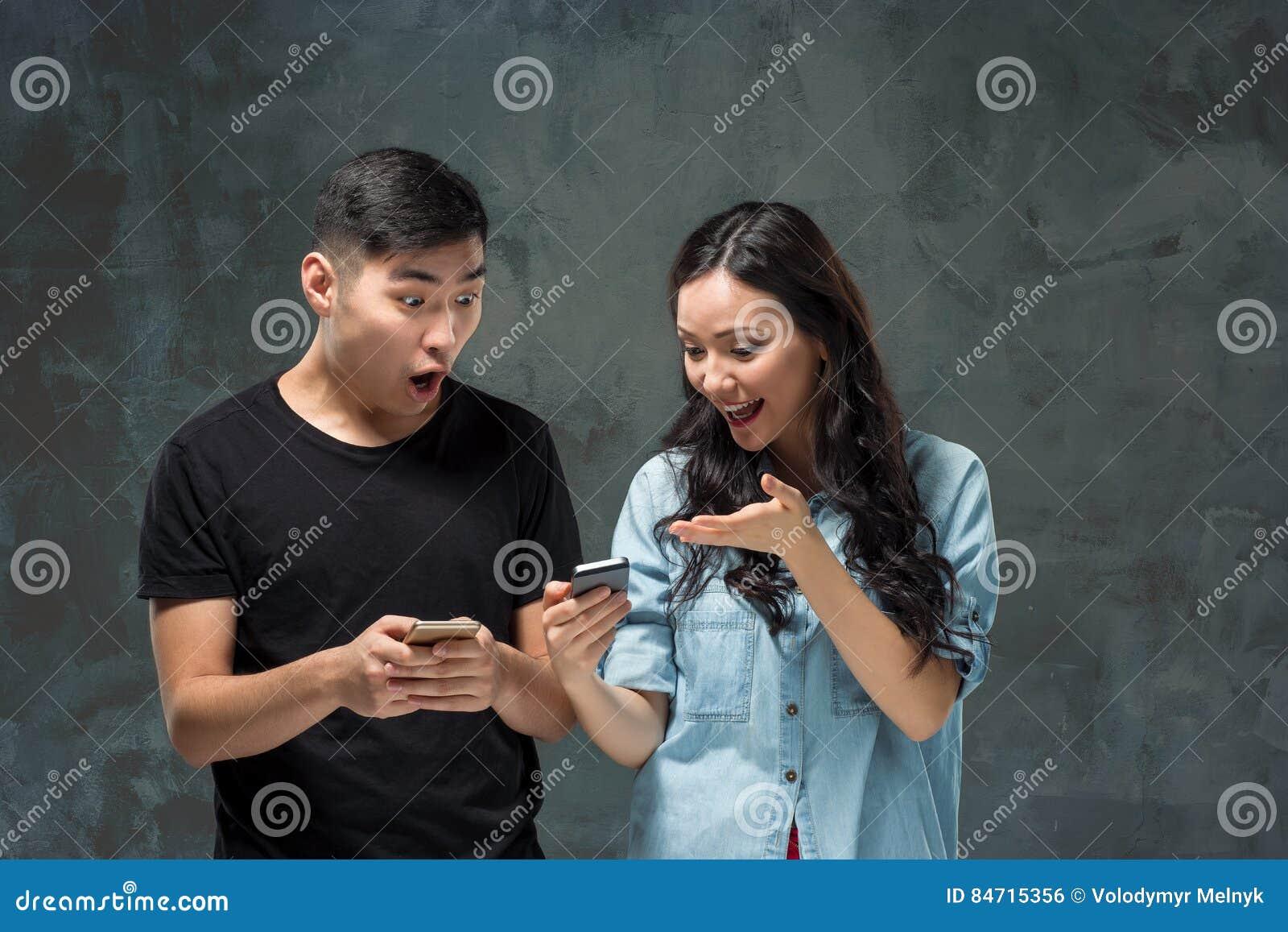 Aziatisch jong paar die cellphone, close-upportret gebruiken