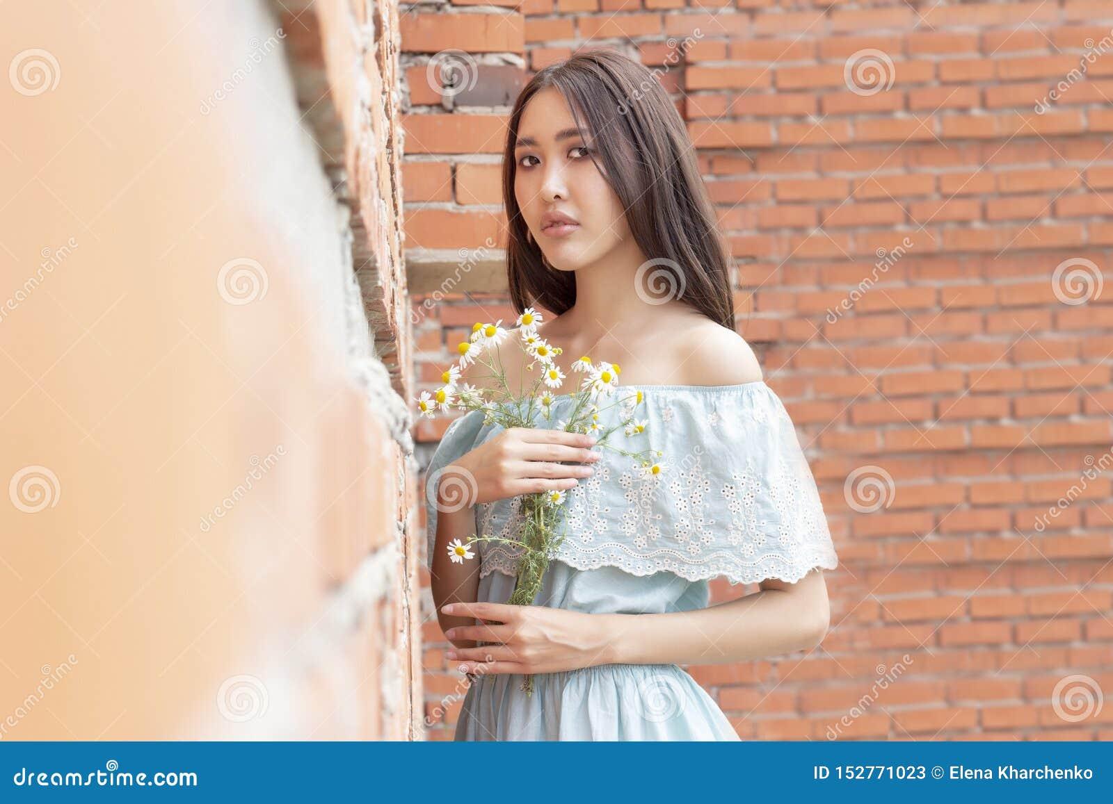 Aziatisch-kijkend meisje met een boeket van kamille in haar handen die zich tegen rode bakstenen muur bevinden