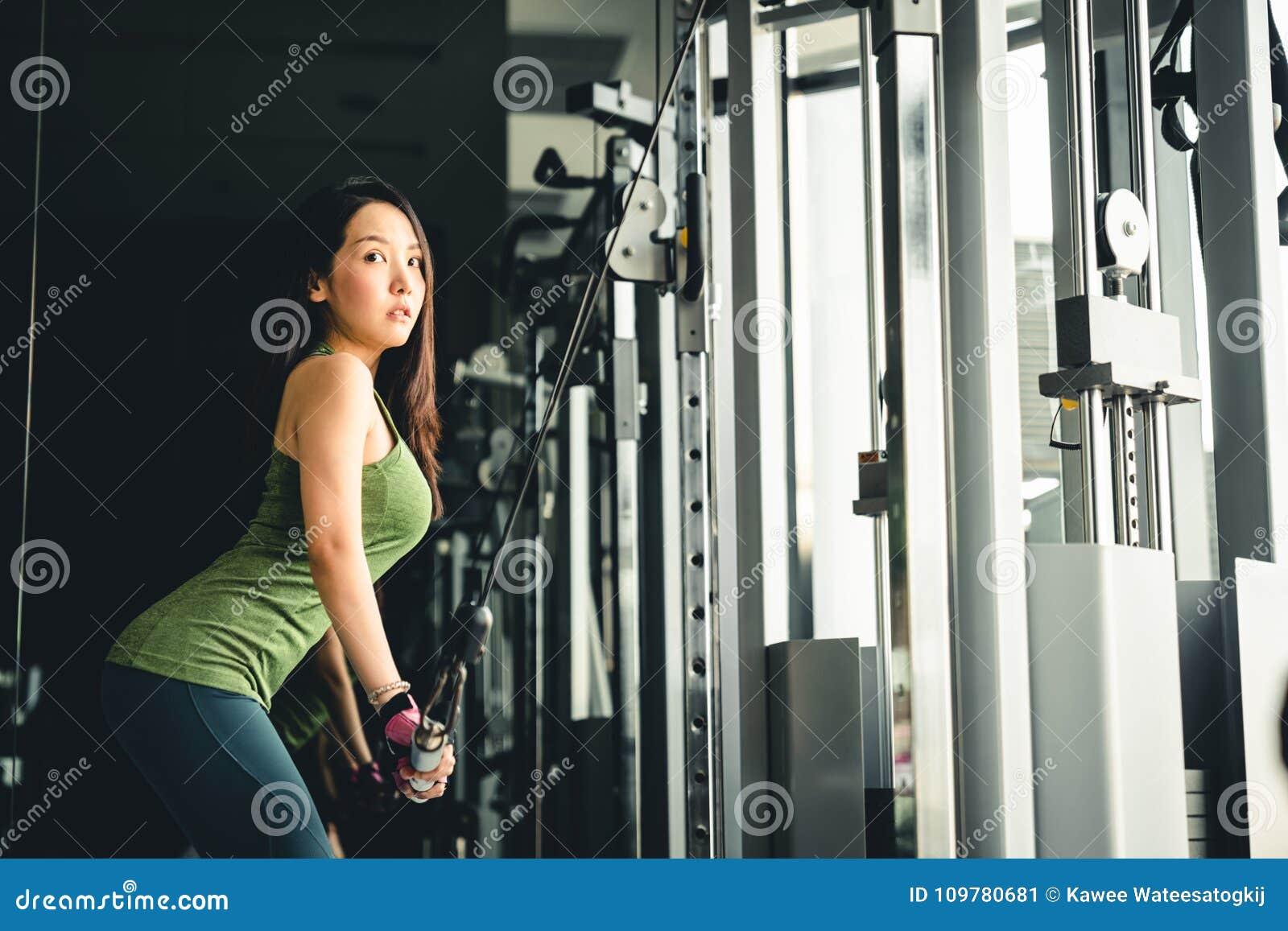 Aziatisch meisje die bij gymnastiek uitoefenen, die op de machine van de pushdownkabel, met exemplaarruimte opleiden Gezonde leve