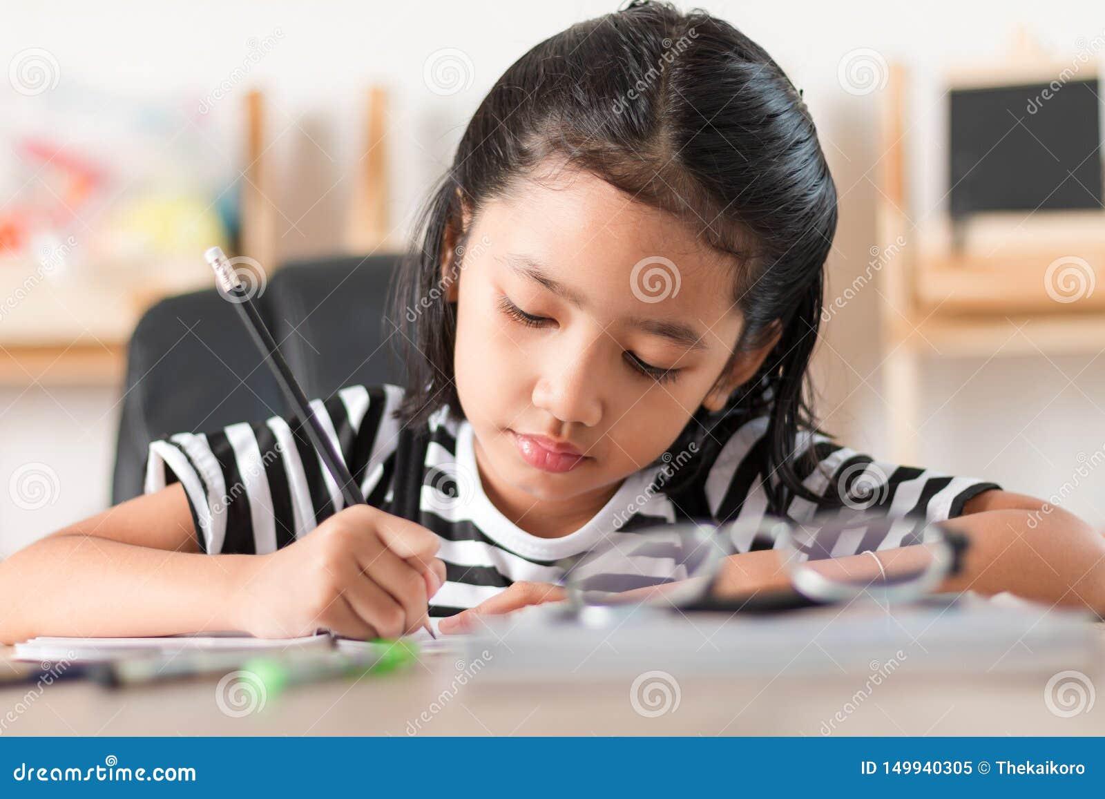 Aziatisch meisje die thuiswerk doen en vinger op de houten ondiepe diepte van de lijst uitgezochte nadruk van gebied richten
