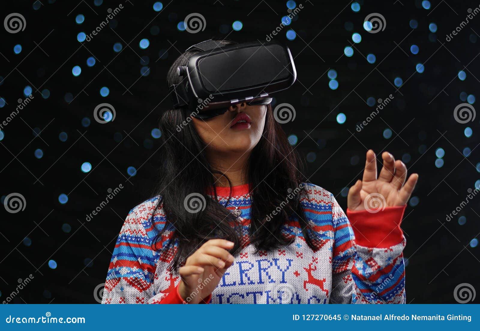Aziatisch Meisje die Virtuele de Sneeuwachtergrond spelen van de Werkelijkheids Donkere Gloed