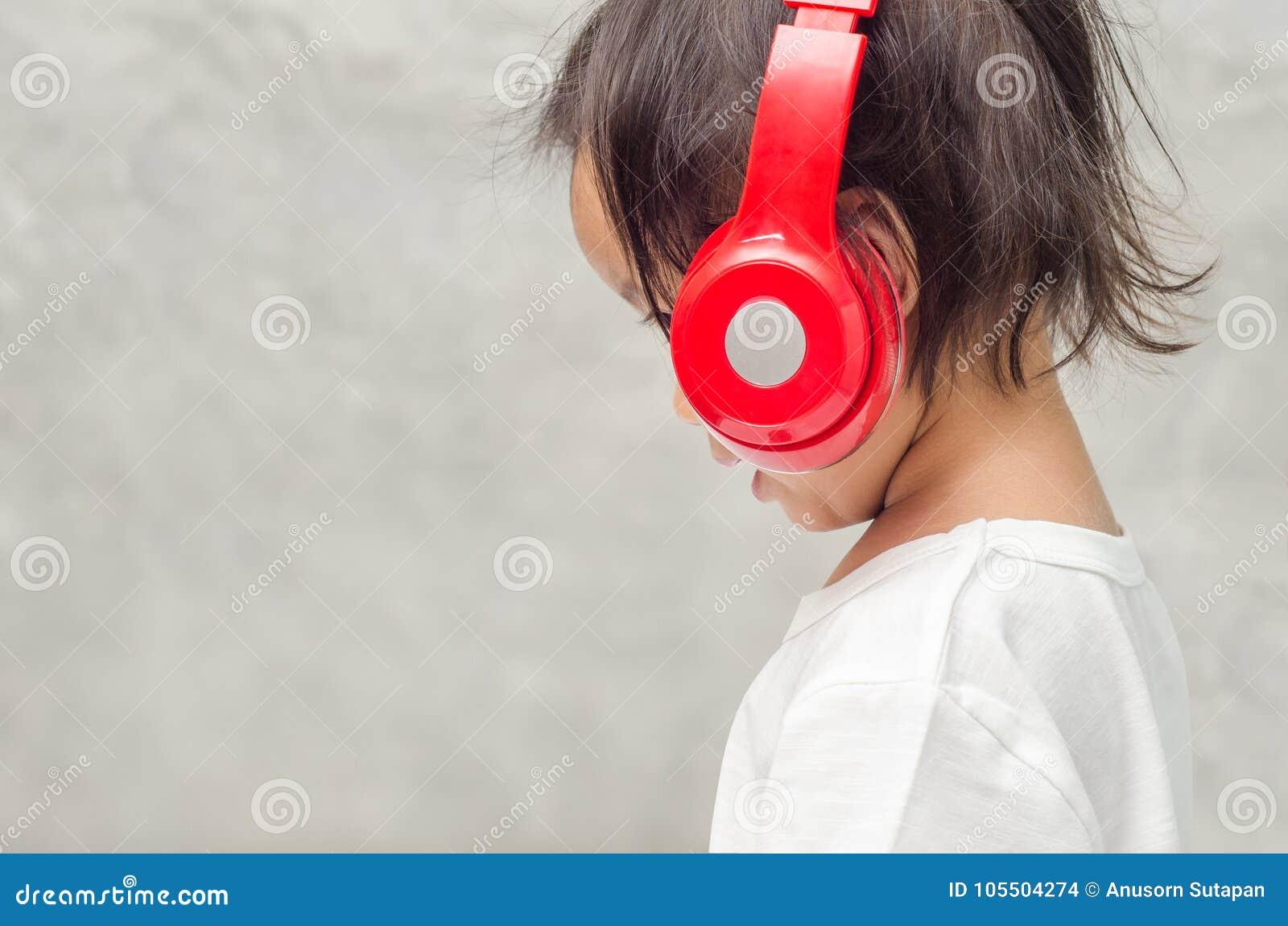 Aziatisch meisje met hoofdtelefoons in de slaapkamer thuis