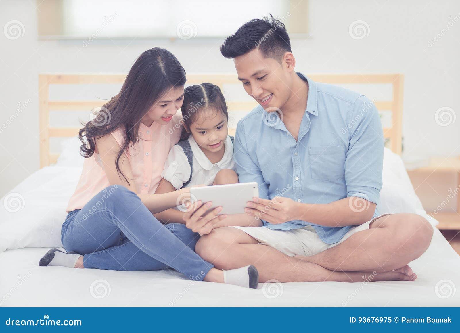 Aziatisch vader en moeder het letten op beeldverhaal met dochter