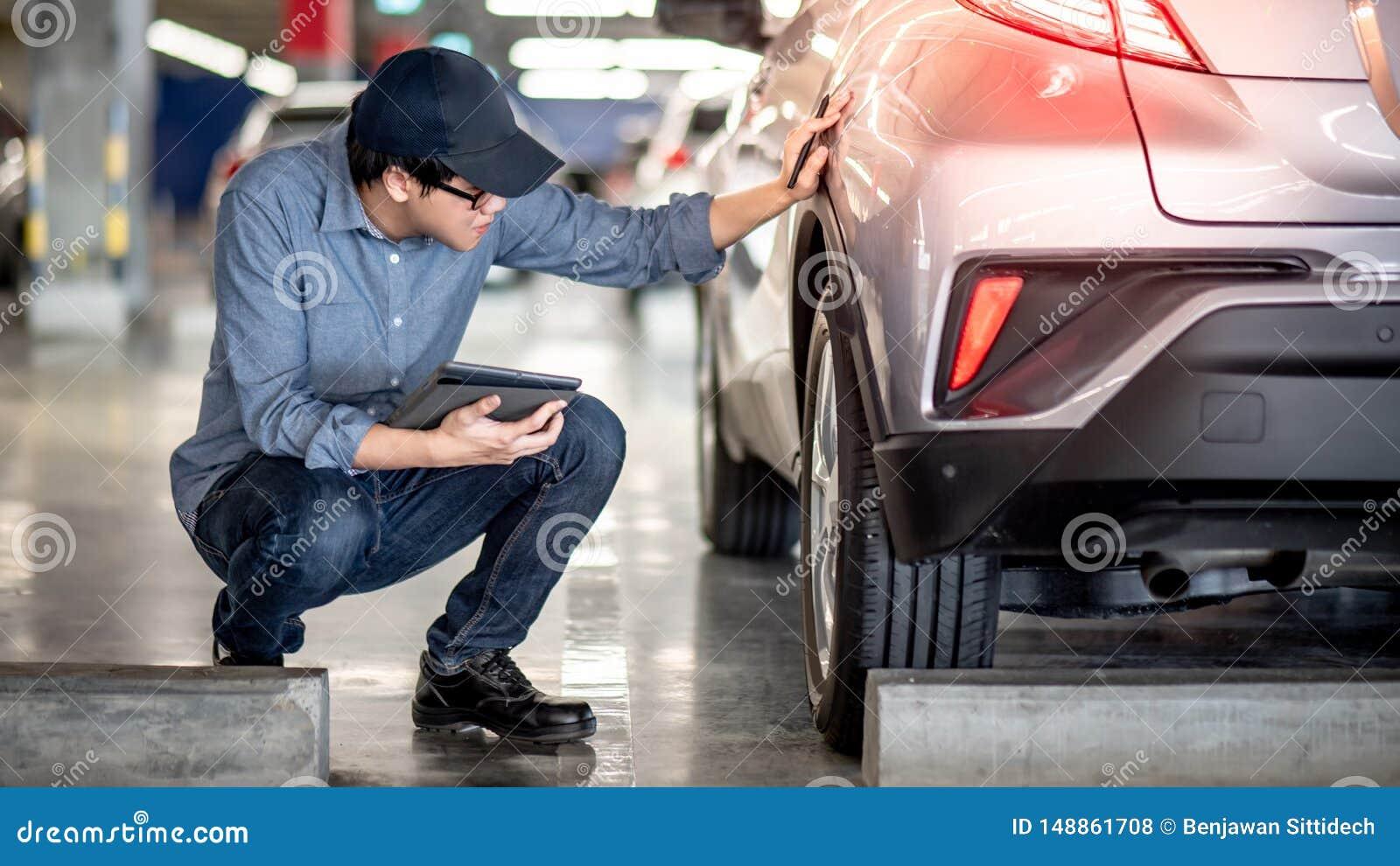 Aziatische autowerktuigkundige die de auto controleren die tablet gebruiken