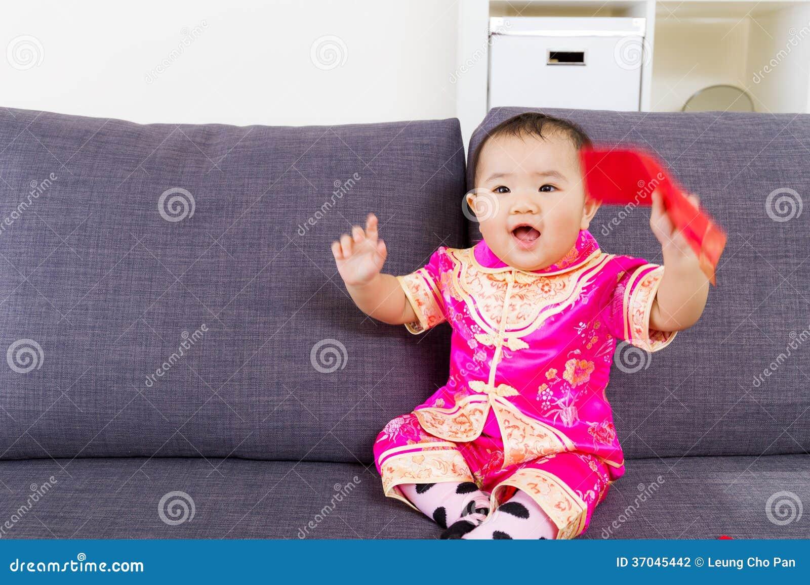 Aziatische baby die rode zak met traditionele Chinese kleding houden