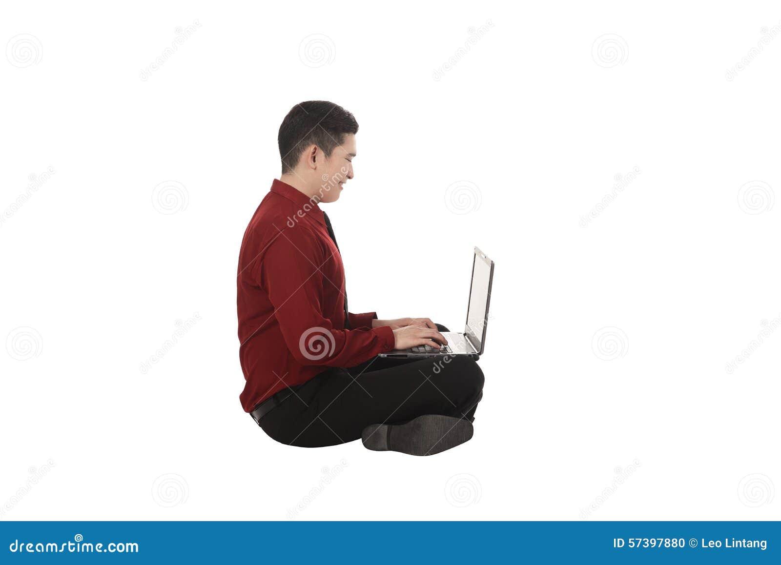 Aziatische bedrijfsmens die aan laptop werken en op de vloer zitten