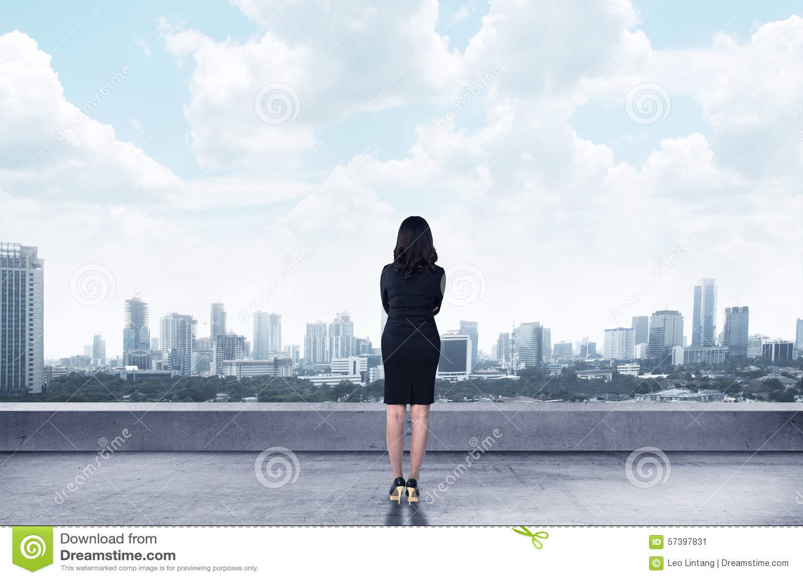Aziatische bedrijfsvrouw die aan de stad kijken